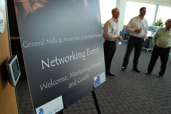 Welcome sign in foreground,  attendees socializing in background