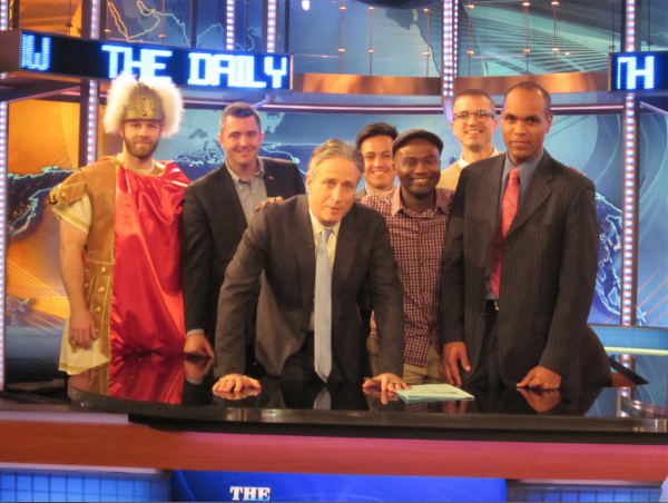 Jon Stewart with 6 of the veterans posing behind the Daily Show desk