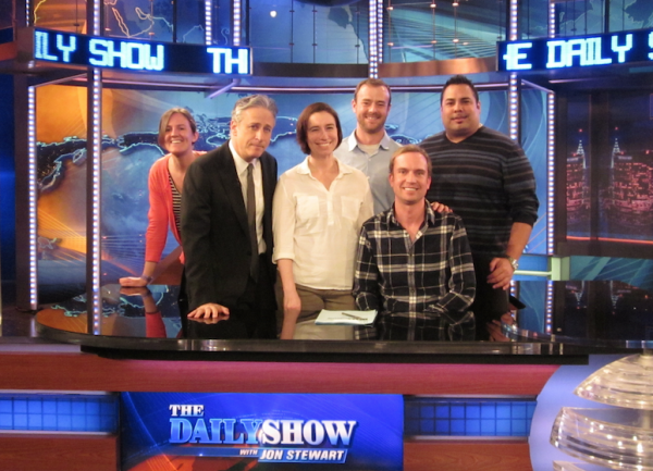 Jon Stewart with 5 of the veterans posing behind the Daily Show desk
